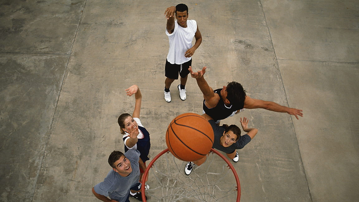 diverse friends playing basketball outdoors