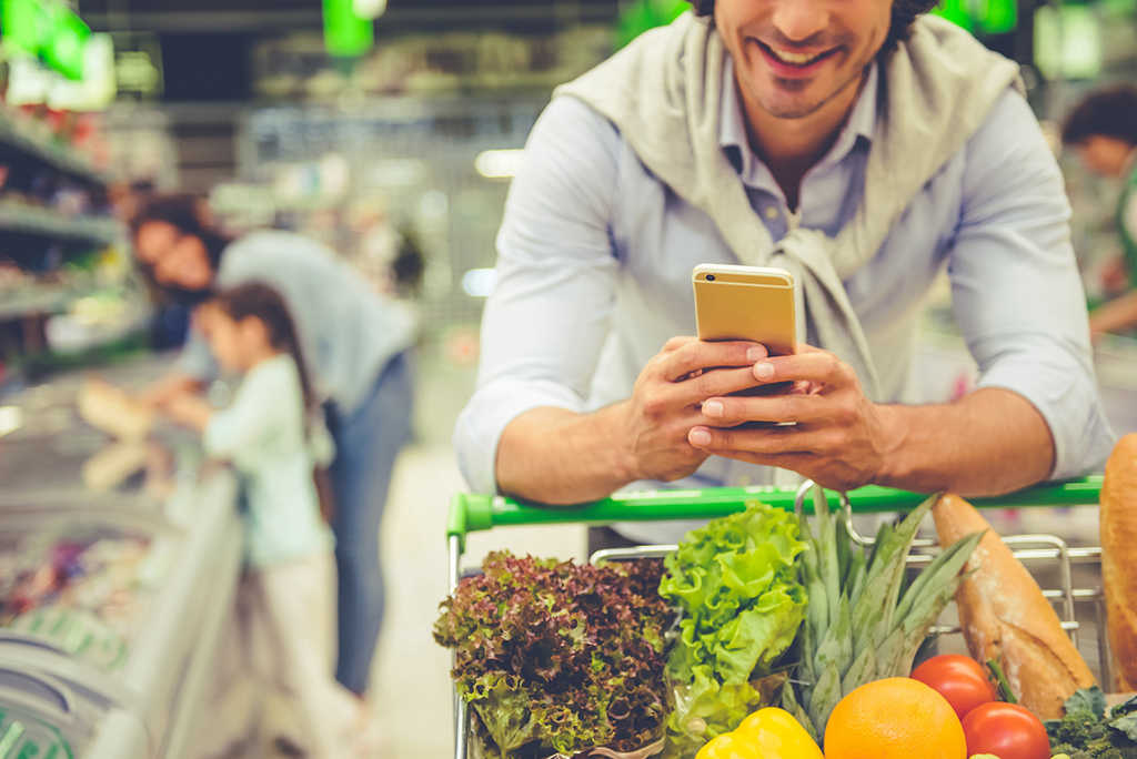 man grocery shopping with phone