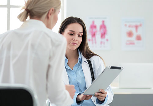 two female doctors looking at clipboard
