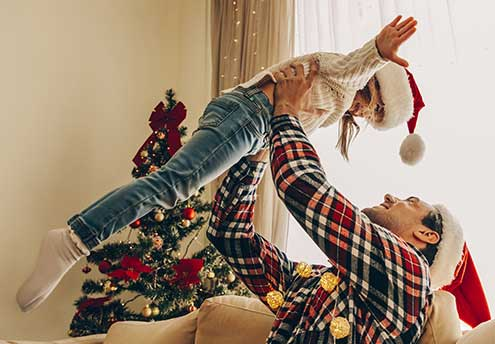 holiday themed photo with dad lifting young daughter above his head like