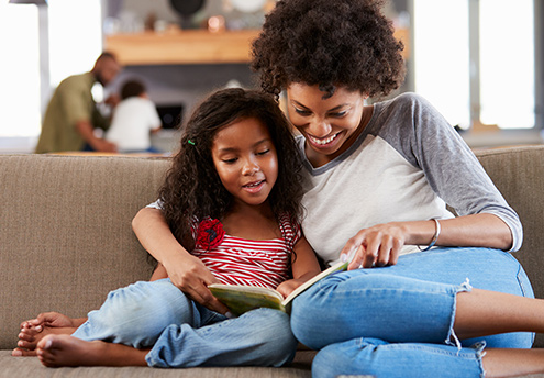 mother and daughter sitting on couch reading a book