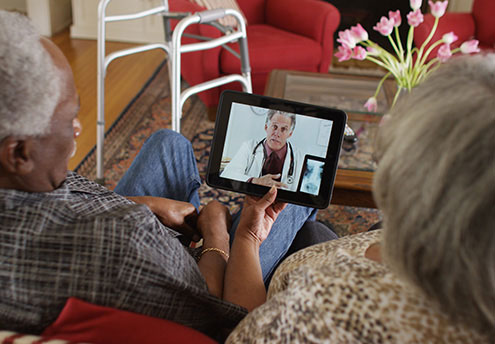 elderly couple looking at ipad