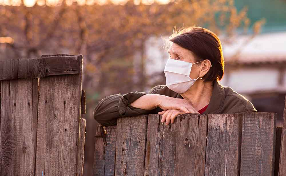 woman wearing protective face mask while looking over fence