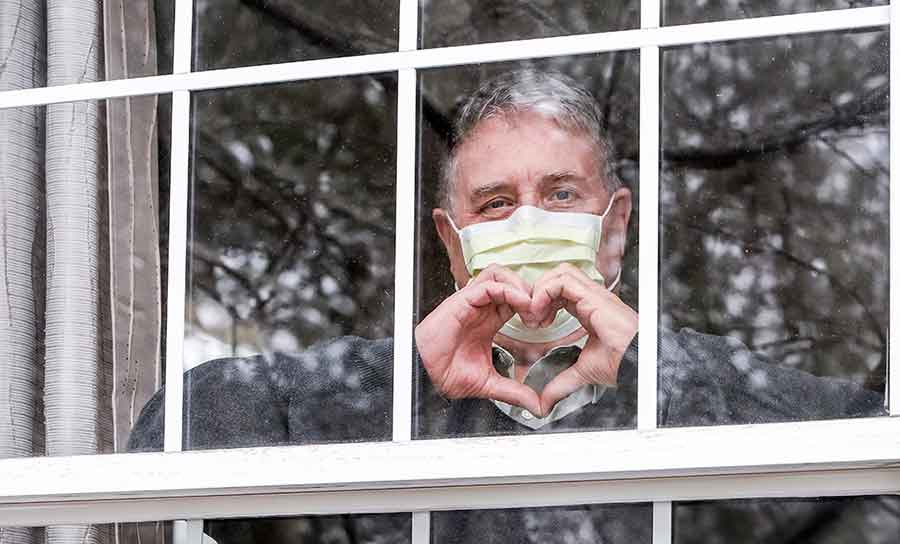 man wearing protective mask looking out window