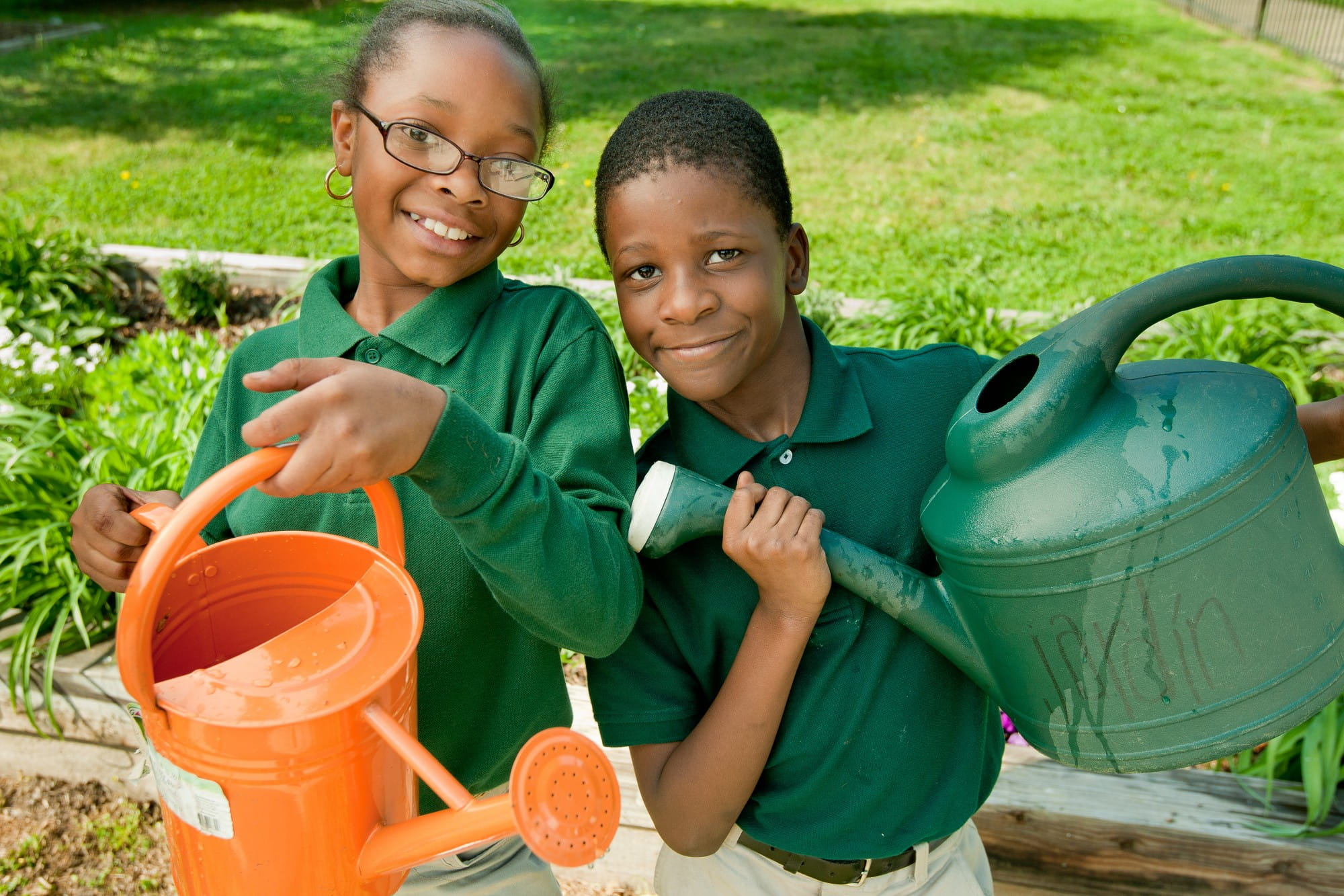 Two students holding watering cans as they participate in school garden program