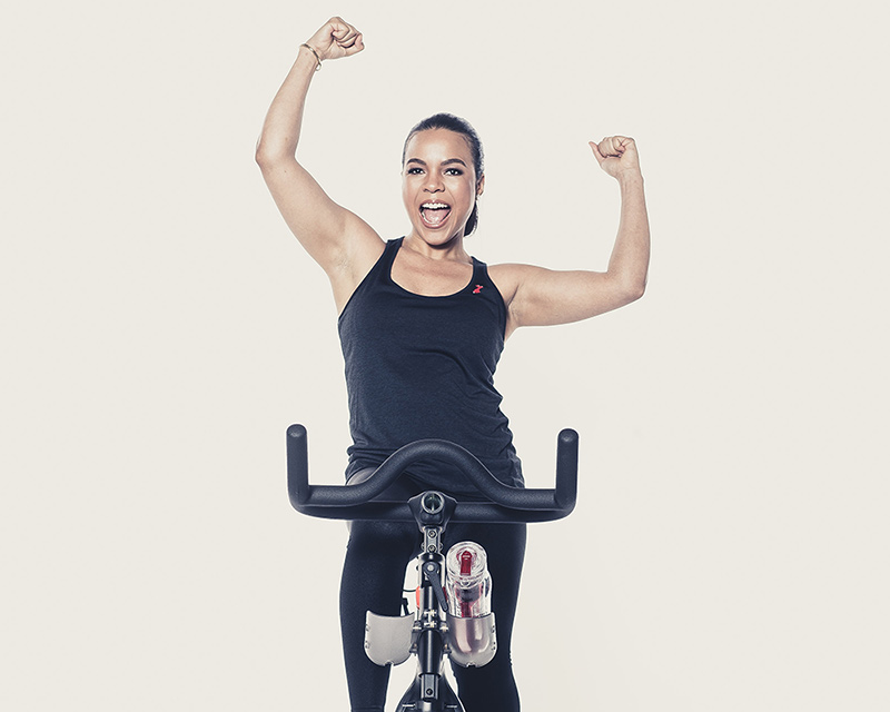 Candy Calderon using an exercise bike and cheering