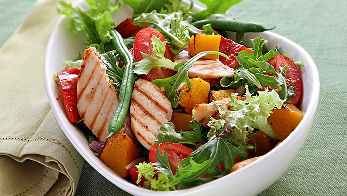 bowl of salad with grilled chicken and peaches