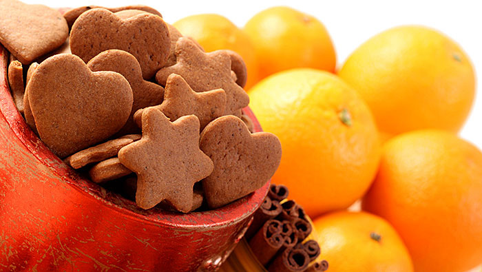 close up of gingerbread cookies, cinnamon sticks, and fresh oranges