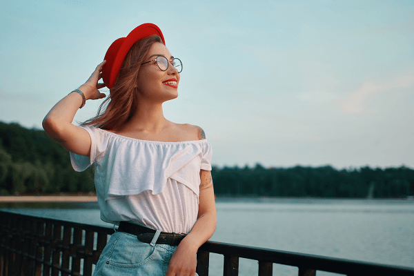 portrait of positive girl with irresistible smile leaning on a rail by a lake