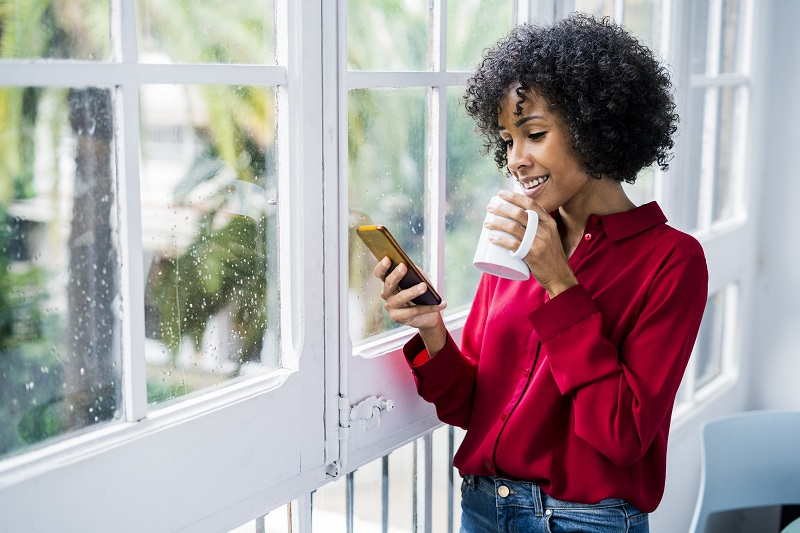 African American woman drinking coffee, looking at cell phone in front of window