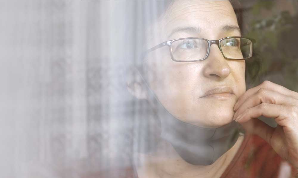 woman wearing protective mask looking out of window