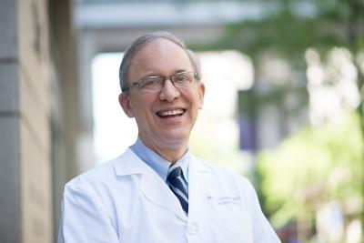 Dr. Neil Stone smiling in white coat