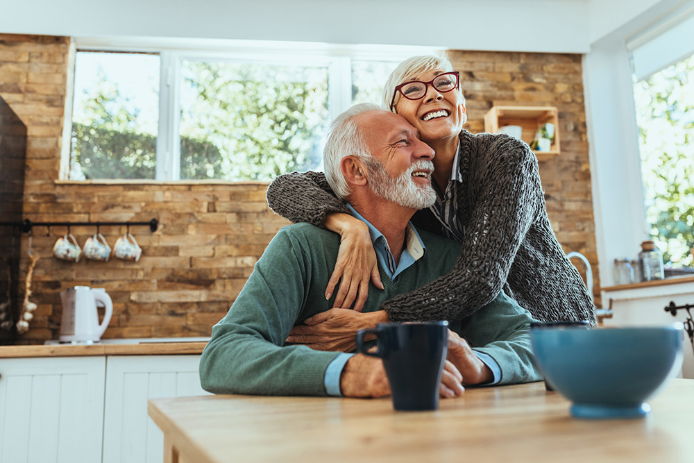 senior couple hugging in kitchen
