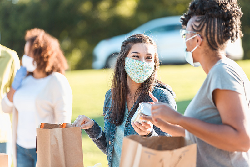 masked volunteers distribute canned food