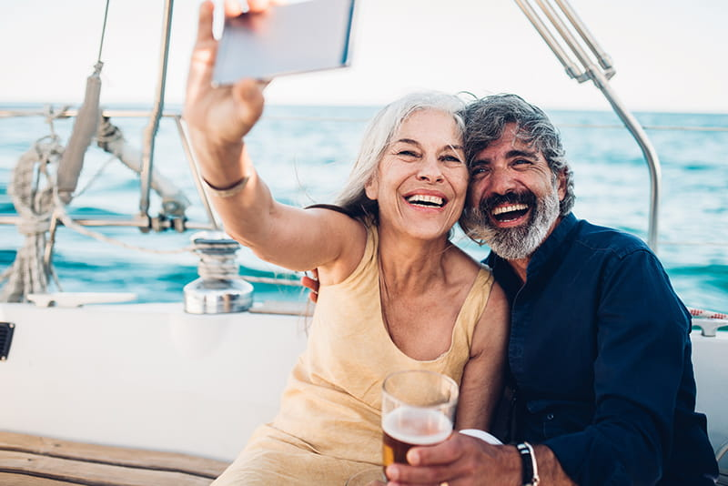 happy couple on sailboat taking selfie