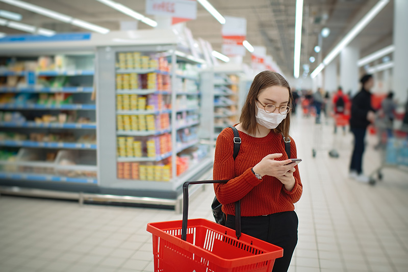 woman shopper reads Heart-Check certified product list while shopping