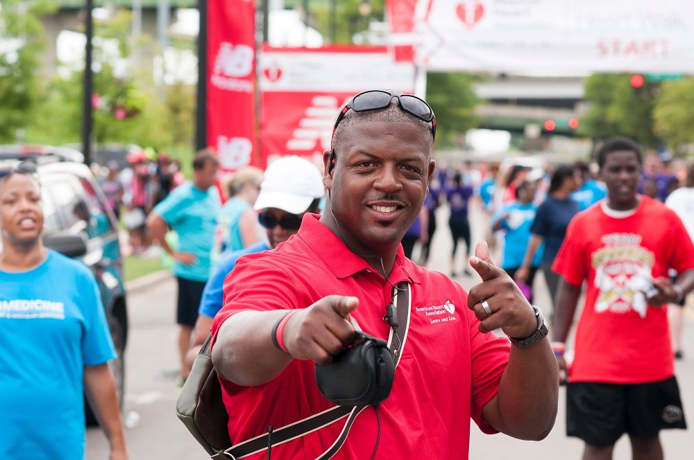 AHA Employee at Heart Walk pointing at the camera and grinning