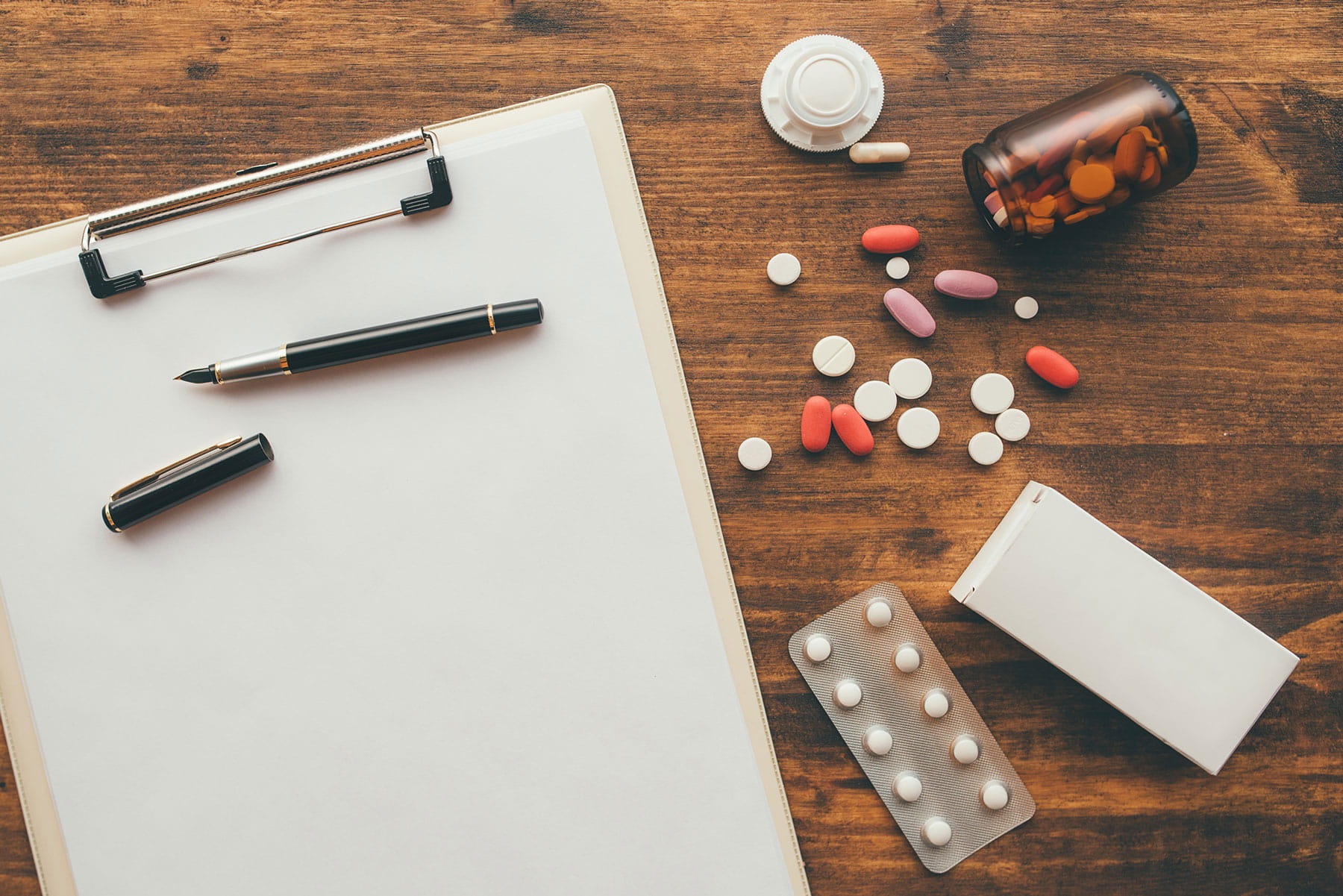 overhead view of medical doctor office desk with medication and notepad