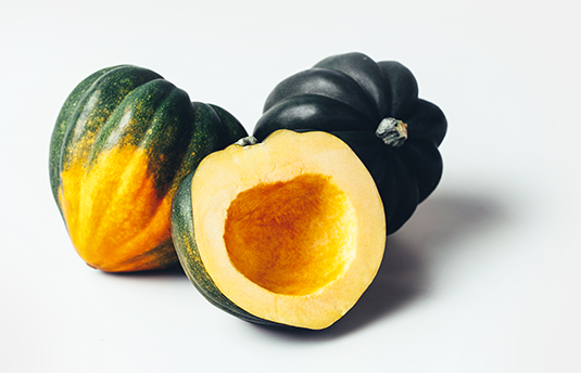 Two whole acorn squashes and one squash cut in half on white table