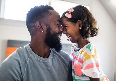 father and daughter forehead to forehead smiling and laughing