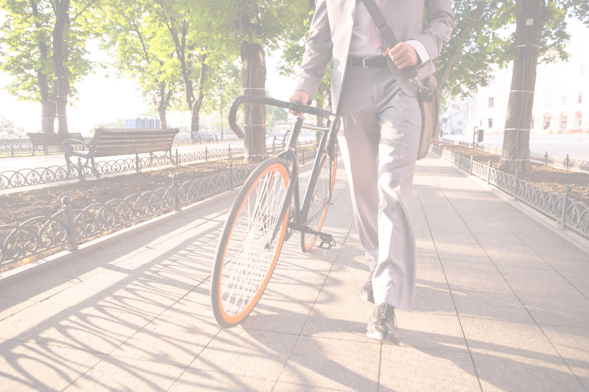 Businessman walking with bike through city park