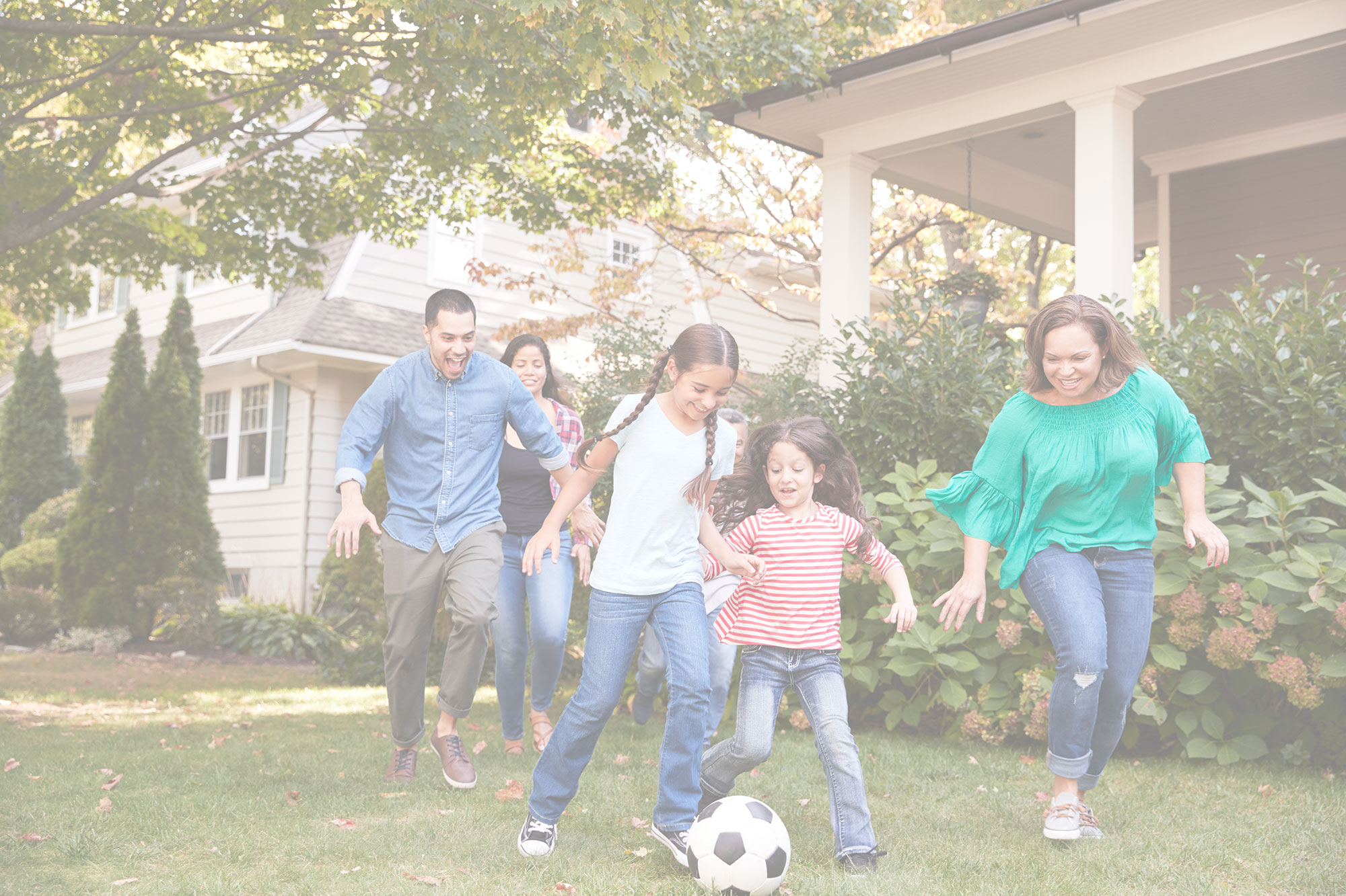 Multi-generational family playing soccer in their front yard