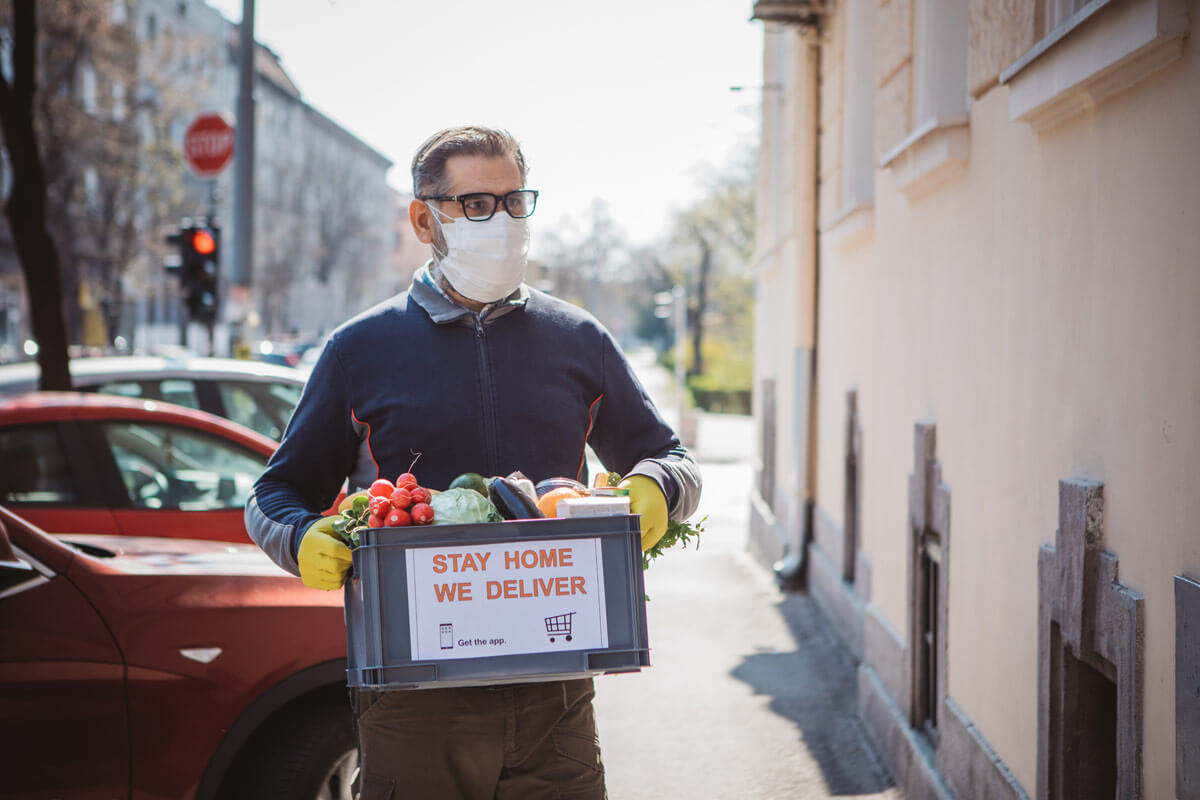 man in mask carrying box of food