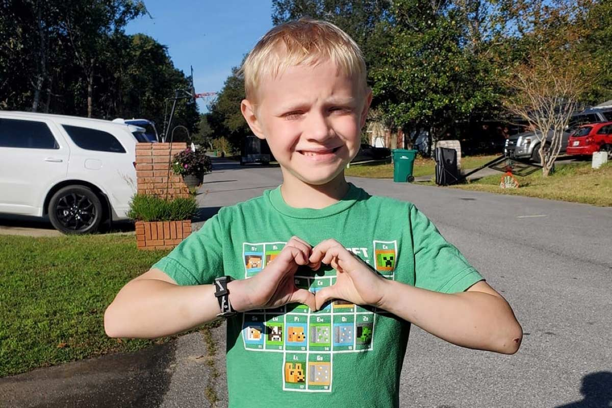 boy holding his hands in the shape of a heart