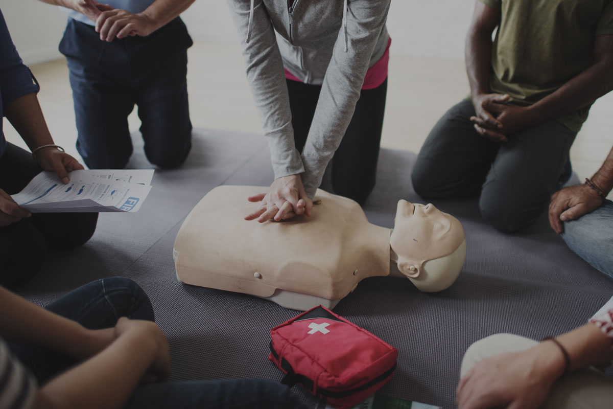 person practicing hands only CPR on dummy with group