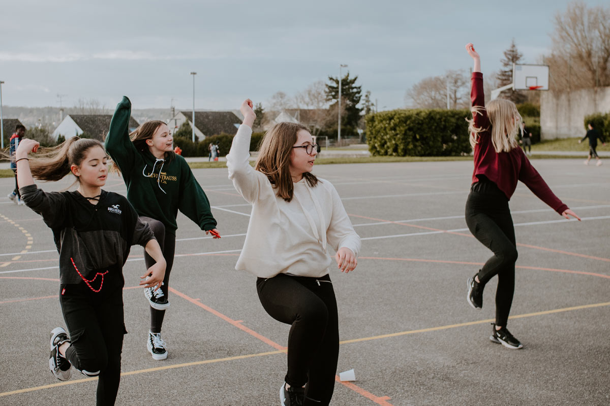 four young women doing synchronized exercise moves outdoors