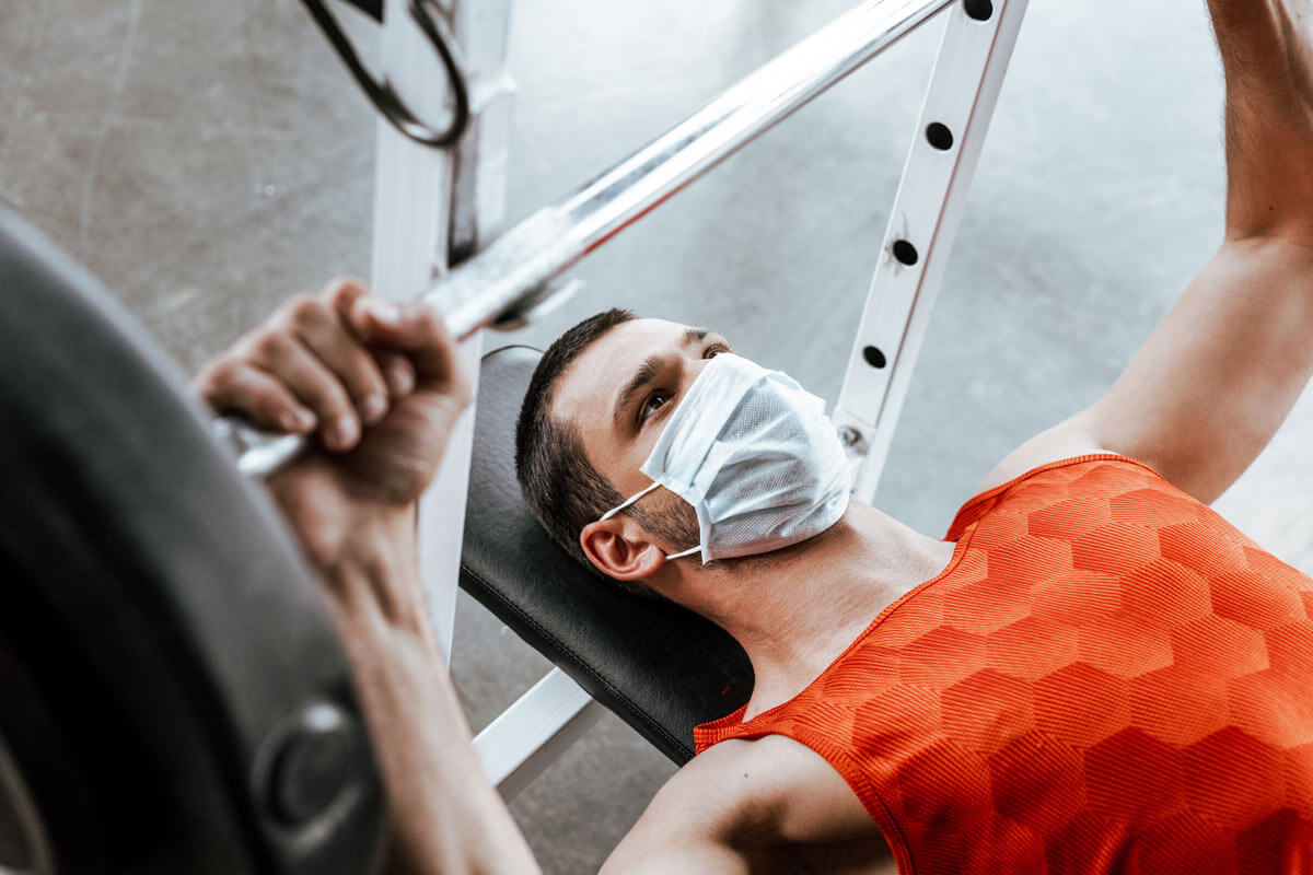 man in mask lifting weights on a bench