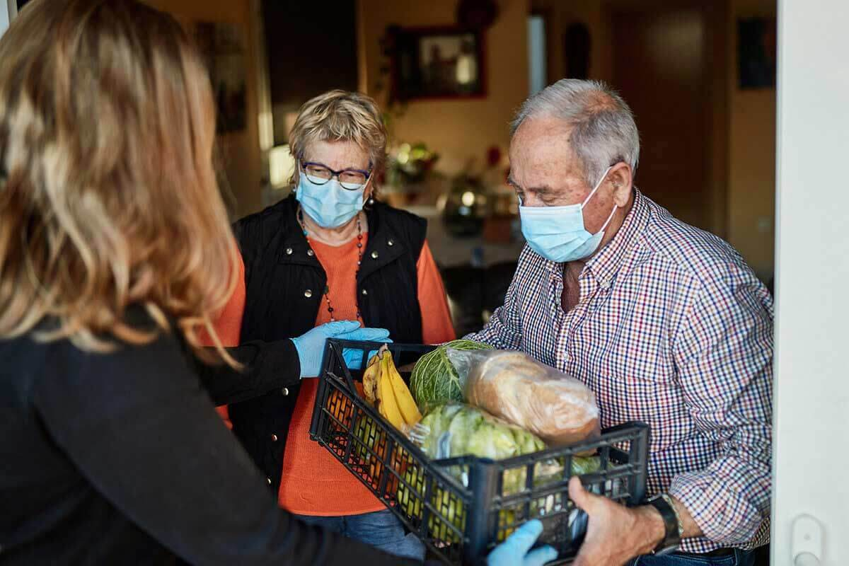 senior couple in masks with box of fresh food