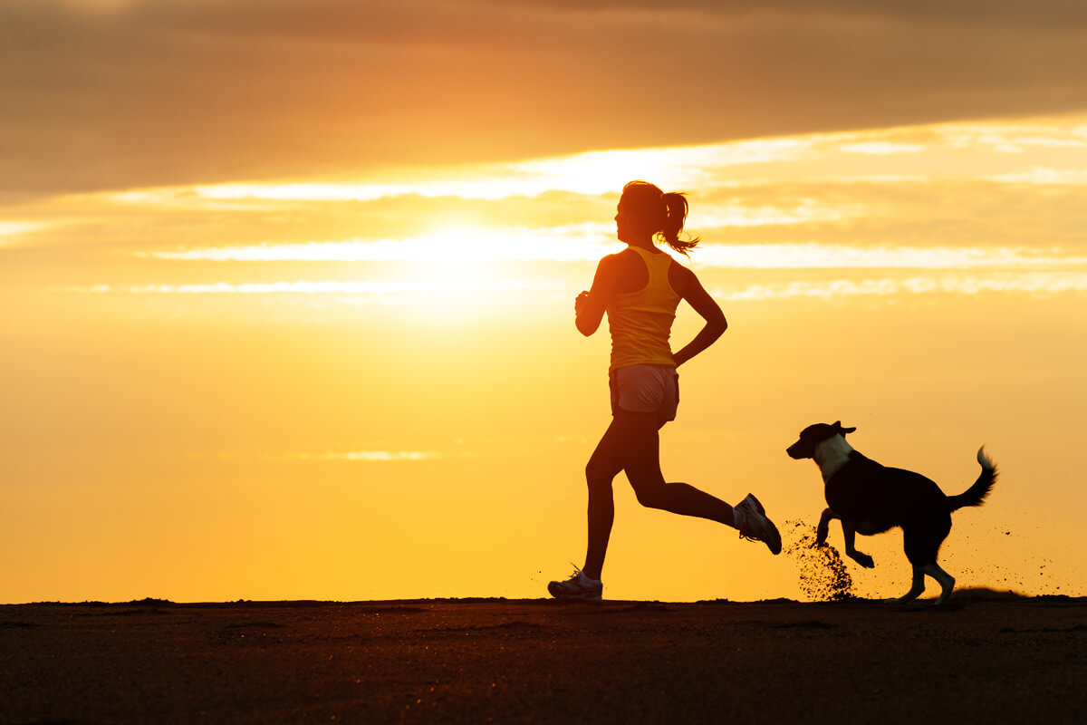 woman running at sunrise with her dog