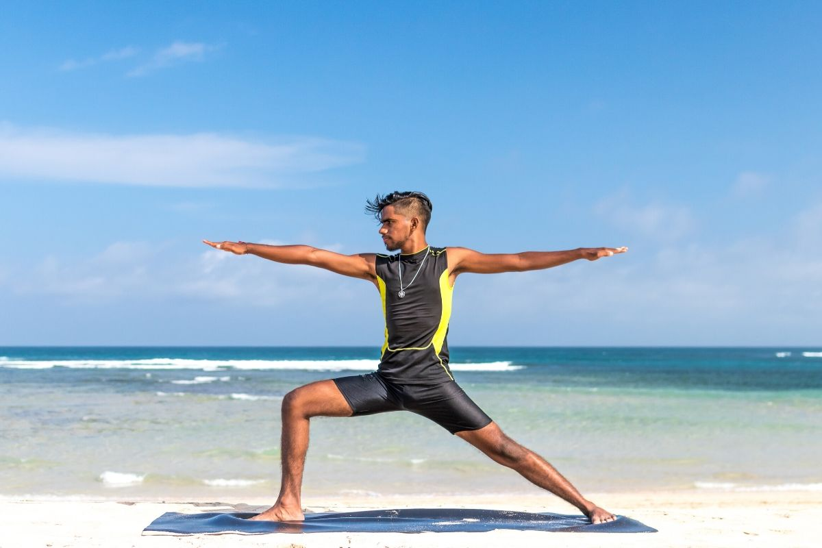 man doing yoga on a beach