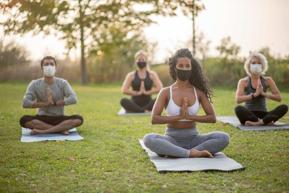 people in masks practicing outdoor yoga