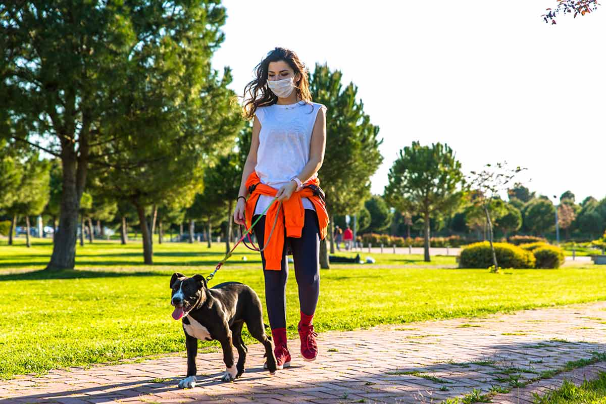 woman in mask walking dog in a park