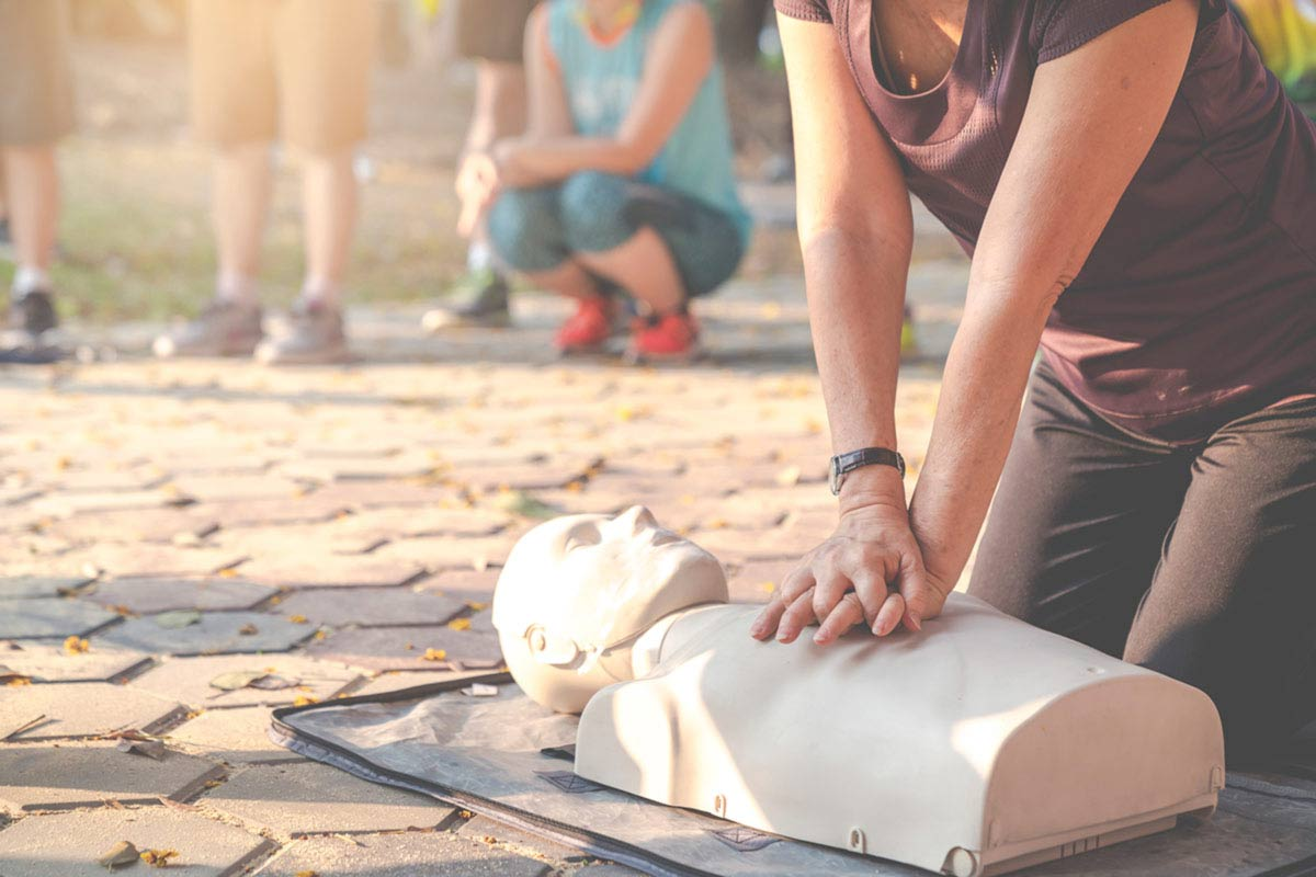 person practicing hands only CPR on mannikin