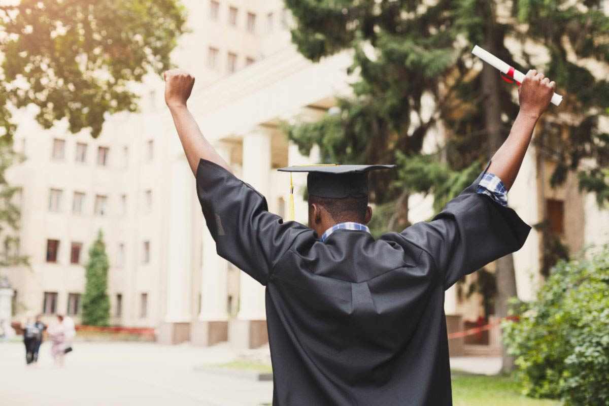 man in graduate cap and gown raising his arms in celebration