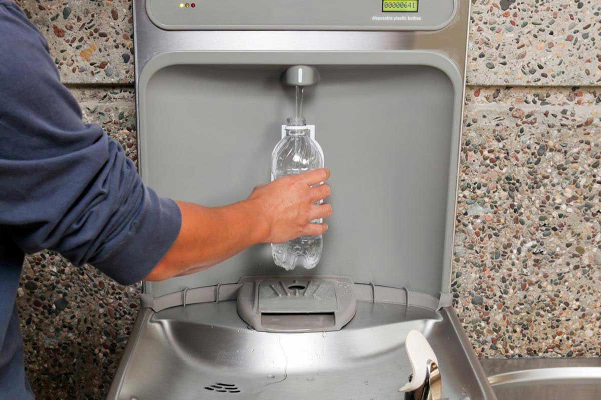 person filling water bottle at water fountain