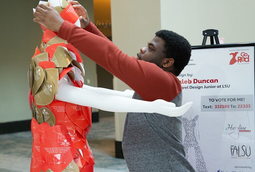 man decorating mannequin for Go Red event