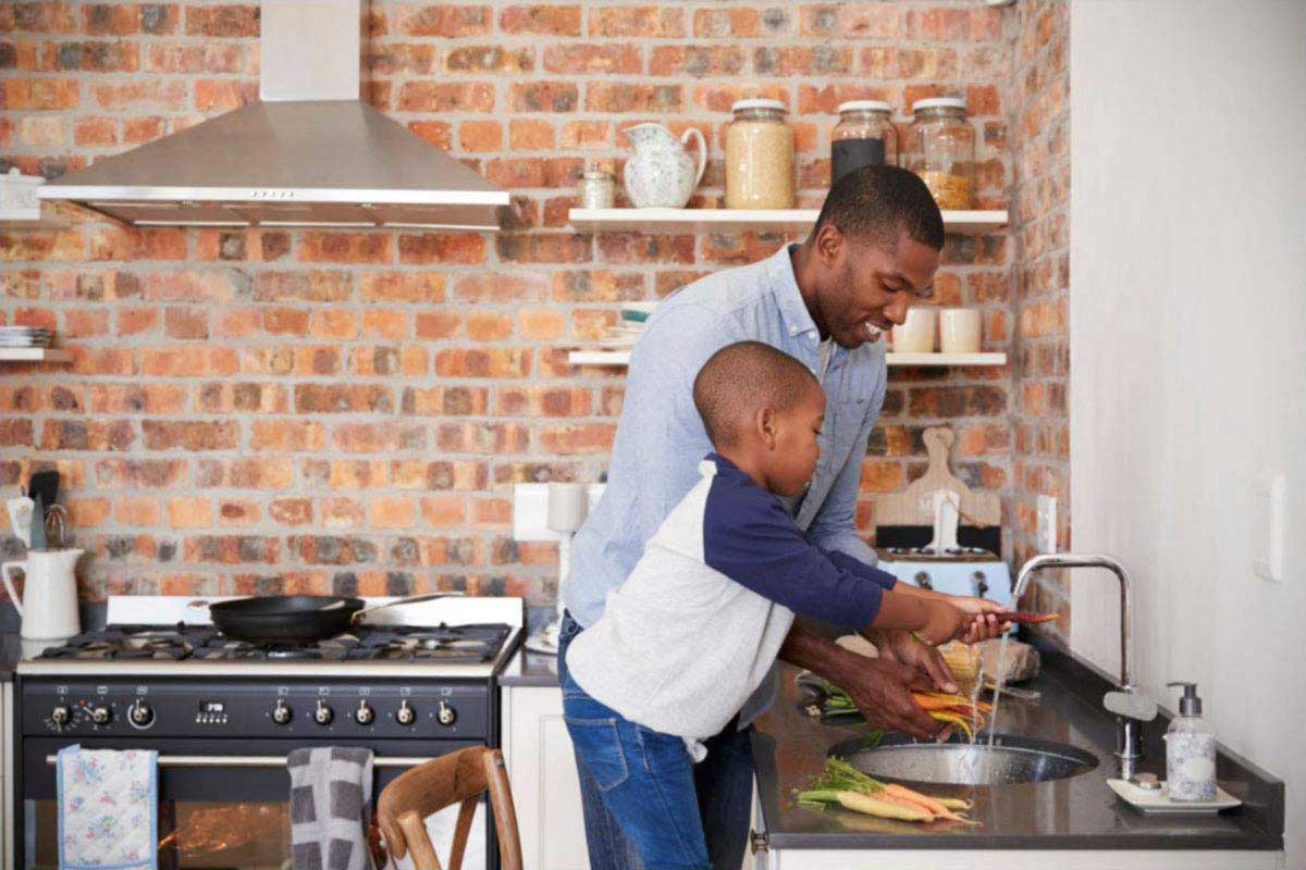 father and son cooking in modern kitchen