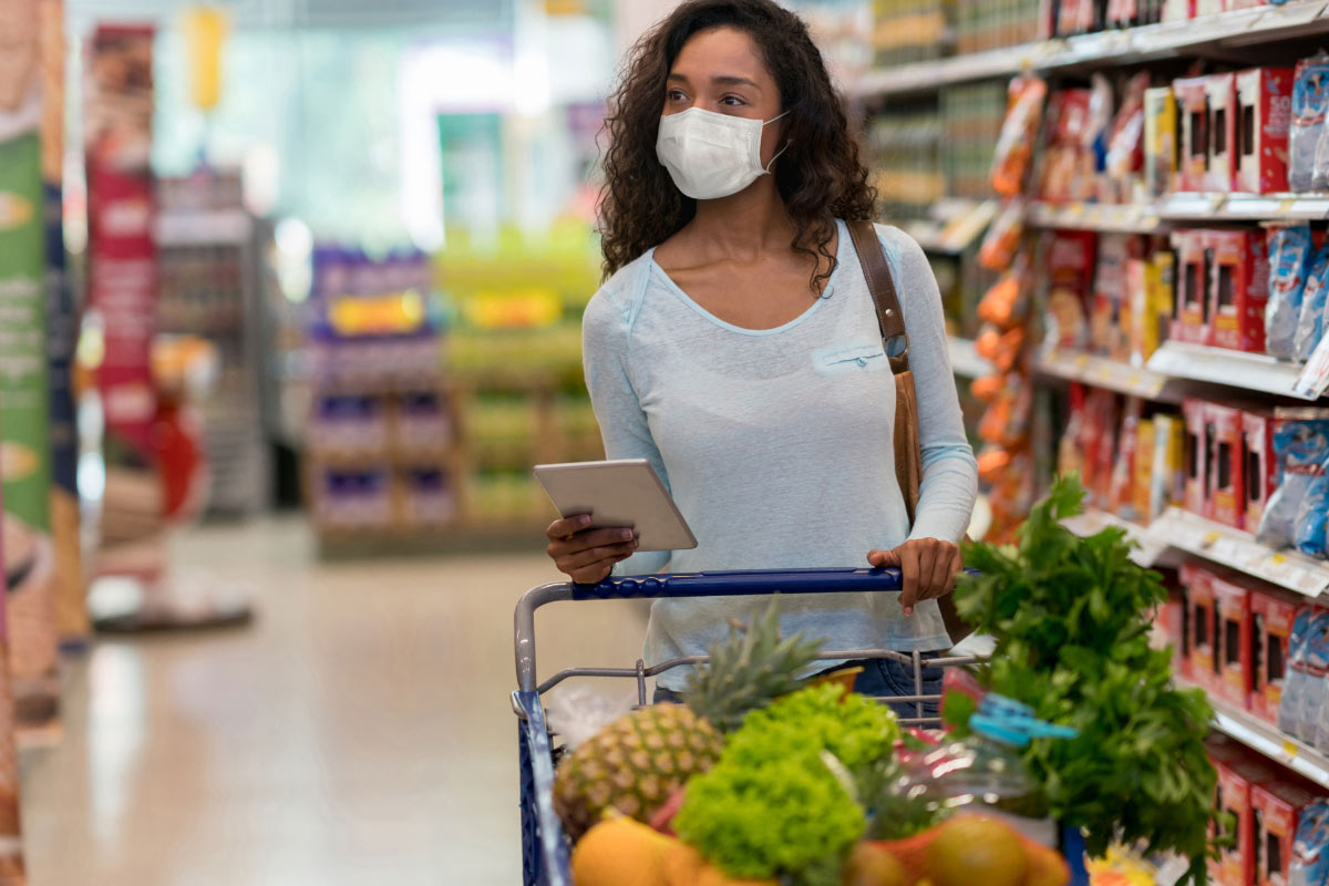 woman in mask pushing grocery cart