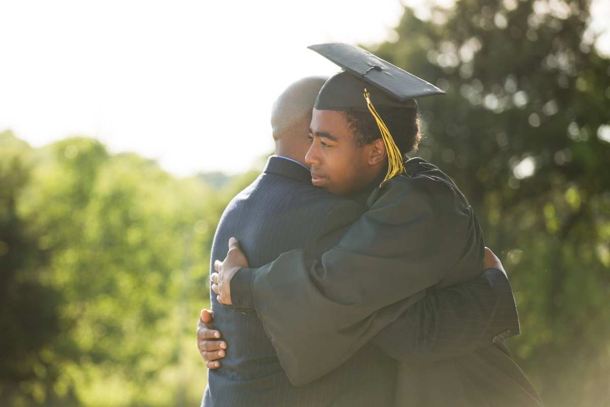 male graduate in cap and gown hugging person