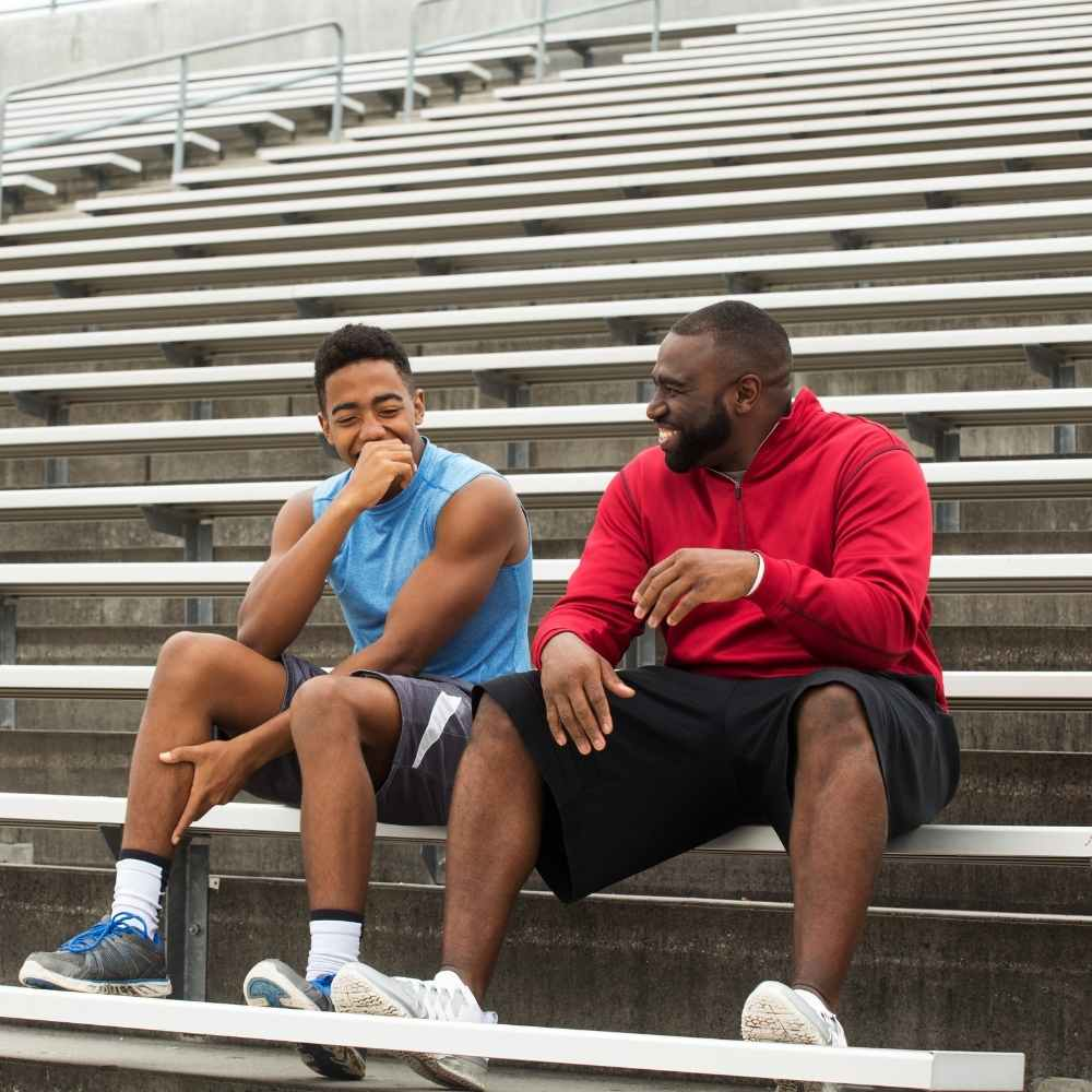 men sitting on bleachers