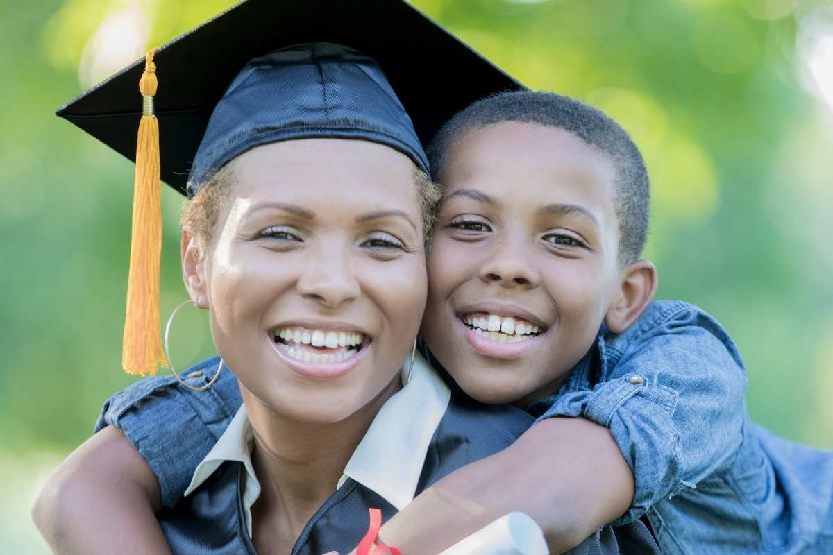 woman wearing graduate cap with boy hugging her