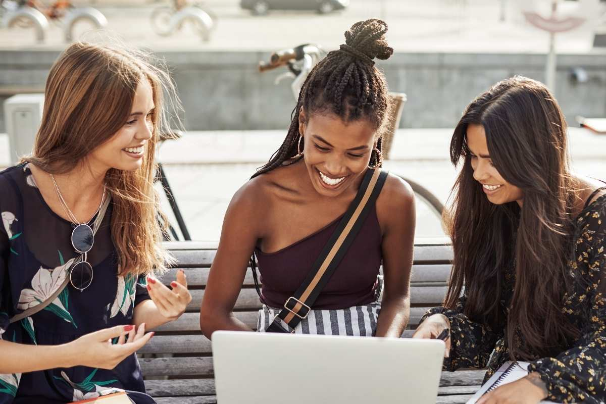 three young women surrounding laptop