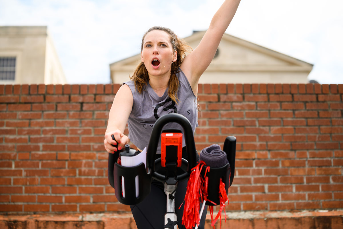 woman on outdoor stationary bike cheering