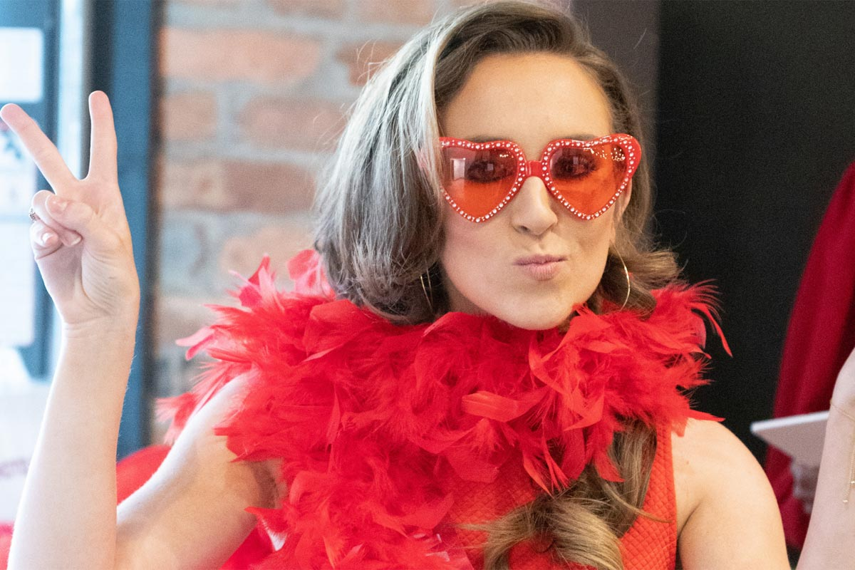 woman in red boa and heart sunglasses holding up peace fingers
