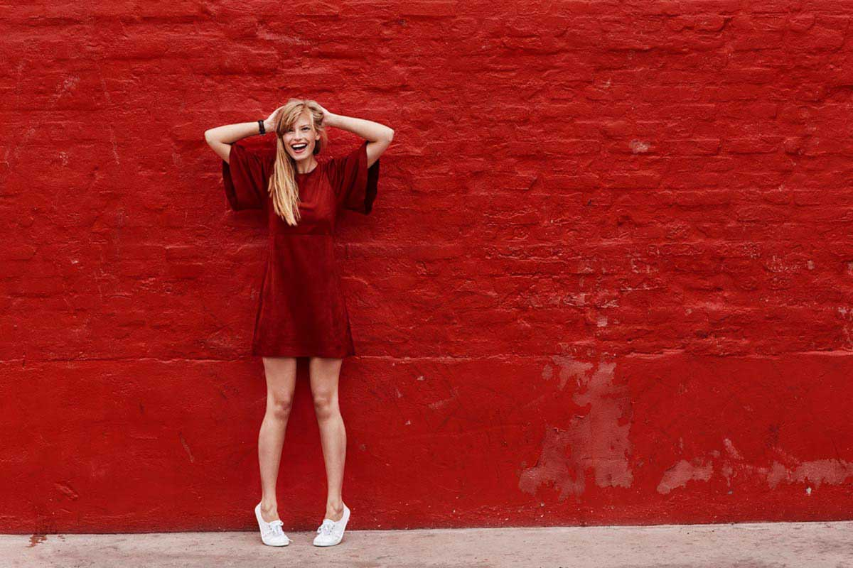 woman in red dress in front of red brick wall