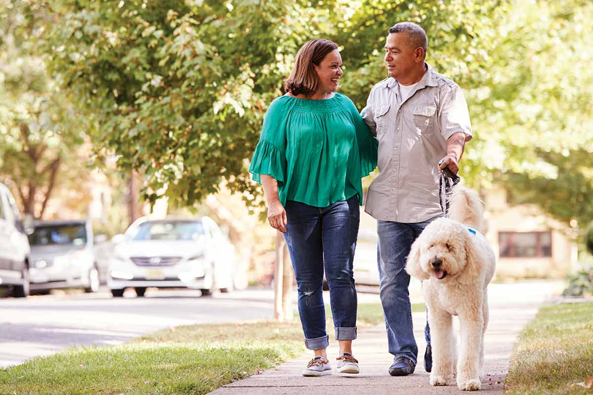 couple walking with dog on a sidewalk